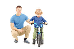 Father near his son trying to riding a bicycle Stock Images