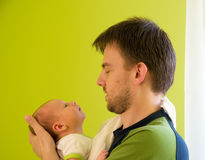 Father with newborn. Five week baby looking straight at its father stock image