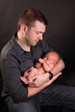 Father with newborn baby. Young father cradling or holding cute newborn baby boy; dark studio background royalty free stock images