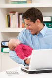 Father With Newborn Baby Working From Home Stock Image