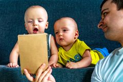 Father with notebook in the foreground. In the background are twins, a boy and a girl of 7 months. Paternity. Father with notebook in the foreground. In the royalty free stock photos