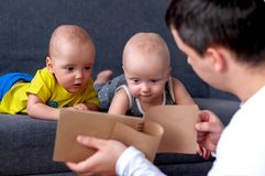 Father with notebook in the foreground. In the background are twins, a boy and a girl of 7 months. Paternity. Father with notebook in the foreground. In the royalty free stock photography