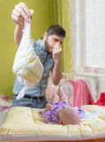 Father od dad is changing diaper that smell. Baby care concept.  Stock Photos