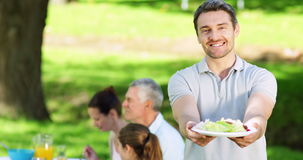 Father offering plate of food to camera at family barbecue Royalty Free Stock Photos