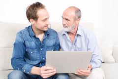 Father and older son. Looking at laptop Stock Images
