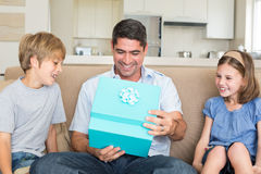 Father opening gift given by children on sofa Stock Image