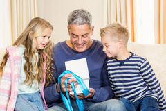 Father opening gift given by children on sofa Royalty Free Stock Photos