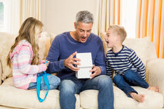 Father opening gift given by children on sofa Stock Photography
