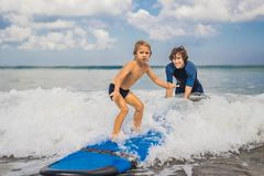Free Father Or Instructor Teaching His 4 Year Old Son How To Surf In Royalty Free Stock Photo - 130925215