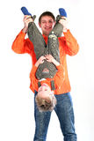 Father in orange clothes holding his child upside Stock Image