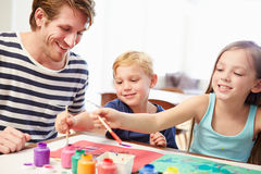 Father Painting Picture With Children At Home Royalty Free Stock Image