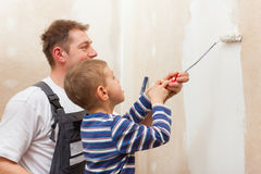 Father painting wall with child. Father and son painting a wall in their home, they presumably do it in the course of moving in stock image