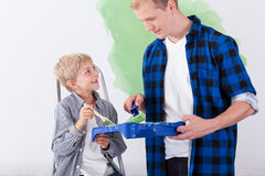 Father painting wall with son Stock Photos