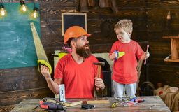 Father, parent with beard in protective helmet teaching little son to use different tools in school workshop. Boy, child. Cheerful playing and learning to use Stock Image