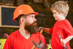 Father, parent with beard in protective helmet teaching little son to use different tools in school workshop. Fatherhood. Concept. Boy, child cheerful holds Stock Photos