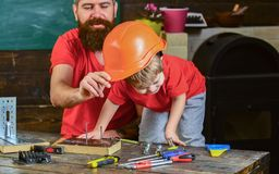 Father, parent with beard teaching little son to use different tools in school workshop. Boy, child busy play with. Protective helmet, learning to use tools royalty free stock image