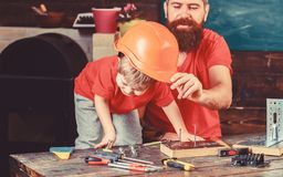 Father, parent with beard teaching little son to use different tools in school workshop. Boy, child busy play with royalty free stock photos
