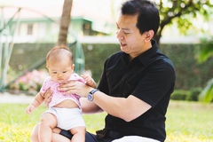 Father parenting baby on park Stock Photography