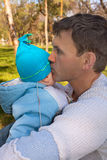 The father in park on a grass sad kisses the son. The daddy in park on a grass sadly and thoughtfully kisses the son Stock Images