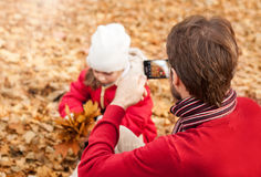 Father photograph his girl child playing in an autumn park Royalty Free Stock Images