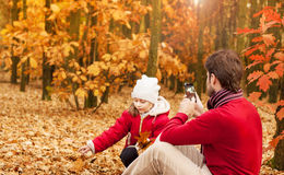Father photograph his girl child playing in an autumn park Stock Photography