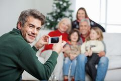 Father Photographing Family Through Mobilephone. Portrait of father photographing family through mobilephone during Christmas at home Stock Image