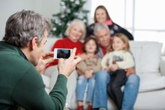 Father Photographing Family Through Smartphone Stock Photo