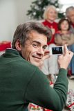 Father Photographing Family Through Smartphone Royalty Free Stock Images
