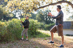 Father photographing son in forest. Father photographing son posing with fishing rod in forest Royalty Free Stock Photo