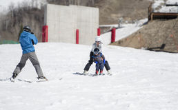 Father Photographs Toddler Son as Mom & Child Ski Downhill. Royalty Free Stock Photography