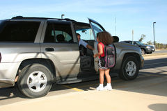 Father picking up girl in SUV Stock Image