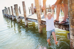 Father on the pier holding son above water, sunny summer Royalty Free Stock Photography