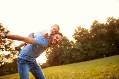 Father piggyback his son outside Stock Image