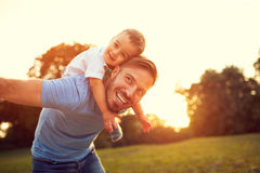 Father piggyback his son outside Stock Photo