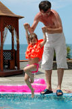 Father play with daughter. Father pulls out daughter from water pool Royalty Free Stock Photo