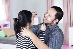 Father play with daughter in the bedroom. Image of Asian father is painting on a face of his daughter with crayons while playing together in the bedroom Stock Photography