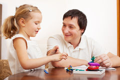 Father play with girl from clay stock images