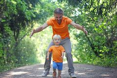 Father play with his little son in summer park. Boy runs away, and his dad catches him. Family look clothing.  royalty free stock photography