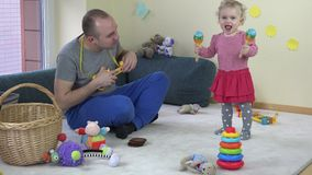 Father play toy guitar and baby daughter shake rattle. stock video footage
