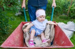 Father playing with baby daughter using trolley on meadow stock images