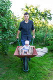 Father playing with baby daughter using trolley in village royalty free stock photo