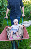 Father playing with baby daughter using trolley in village stock photos