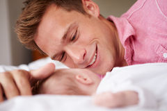 Father Playing With Baby Girl As They Lie In Bed Together Stock Photo