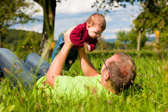 Father playing with baby on meadow Royalty Free Stock Image