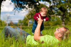 Father playing with baby on meadow Royalty Free Stock Photography