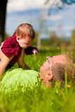 Father playing with baby on meadow Stock Photo
