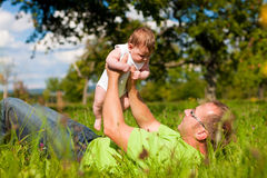 Father playing with baby on meadow Stock Photography
