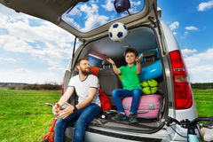 Father playing ball with son sitting in car boot. Active father playing ball with his son sitting in the car boot full of luggage Stock Image