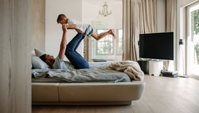 Father playing in bed with son. Man holding a little boy on his legs in bedroom Royalty Free Stock Photography