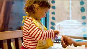 Father playing with cheerful small girl. Baby gives toy horse to drink and father's hand holding a toy bucket. Close up stock video